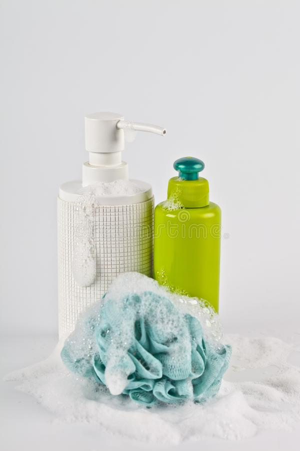 Bath cosmetic products, green sponge and foam on light background stock image
