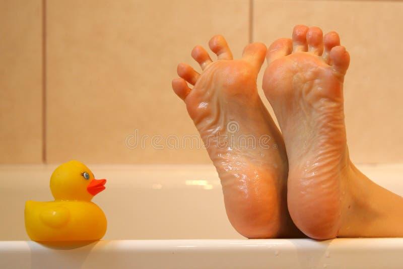 Bath duck meeting feet royalty free stock photos