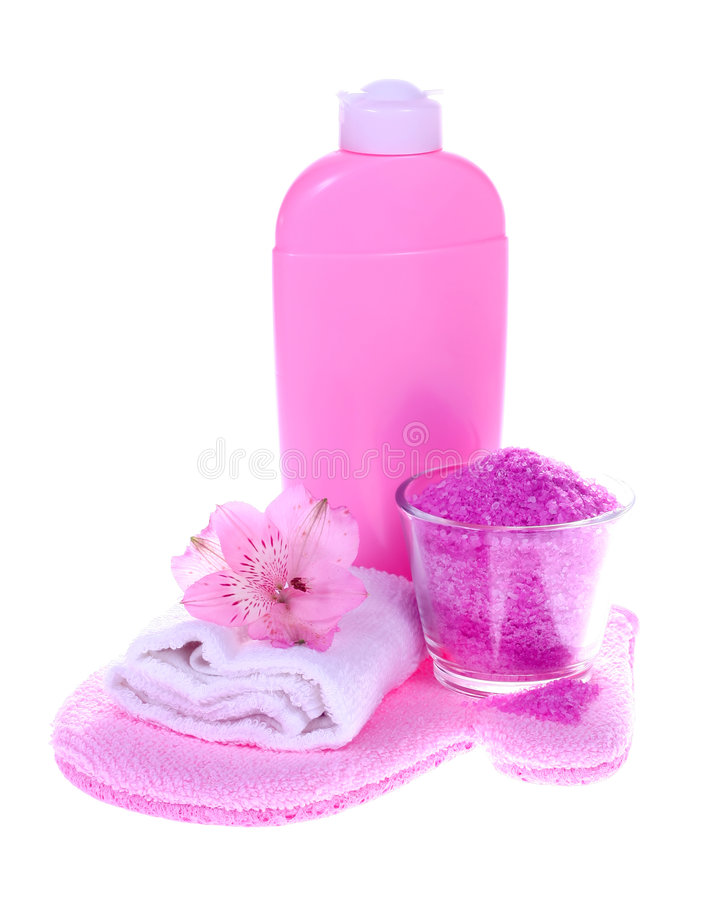 Bath essentials. Pink bathroom composition with liquid soap, bath salt, towel, scrubbing glove and flower (isolated on white background stock image