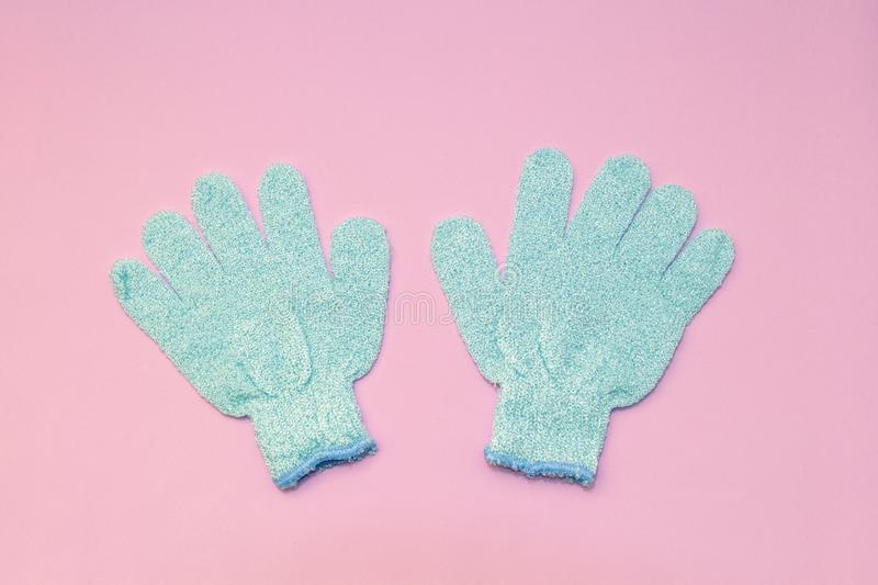 Bath massage blue gloves for shower with exfoliating hydro peeling scrub effect on soft pink background. Top view, flat lay.  royalty free stock images