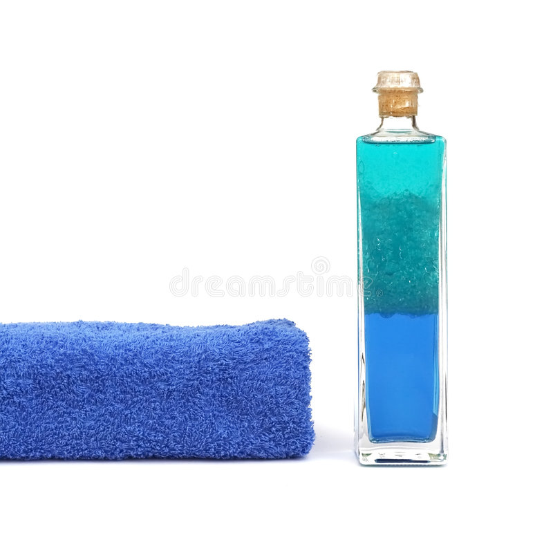 Bath oil. A bottle of bath oil and a blue towell royalty free stock photos