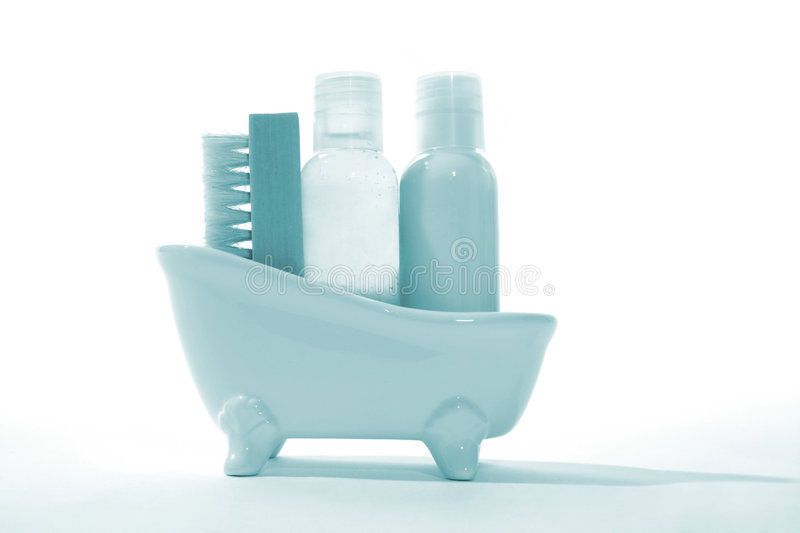 Bath Products. Shampoo, conditioner, and brush inside a miniature bathtub stock photography