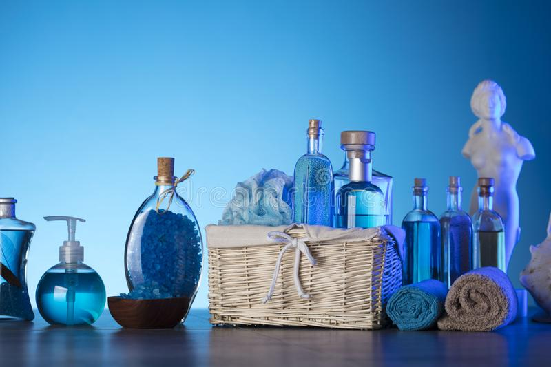 Bath and spa concept. Difeerent cosmetics on stone table and blue background royalty free stock image