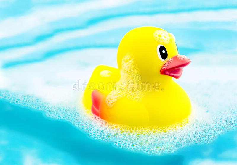 Bath time and rubber duck in soap foam. Bath time cocncept image with yellow rubber duck on water and soap foam stock images