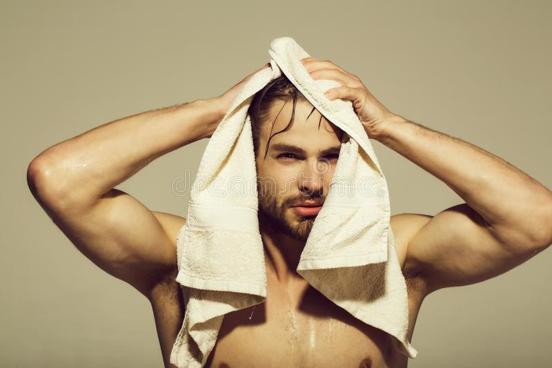 Bath towel at naked man with muscular wet body stock photo