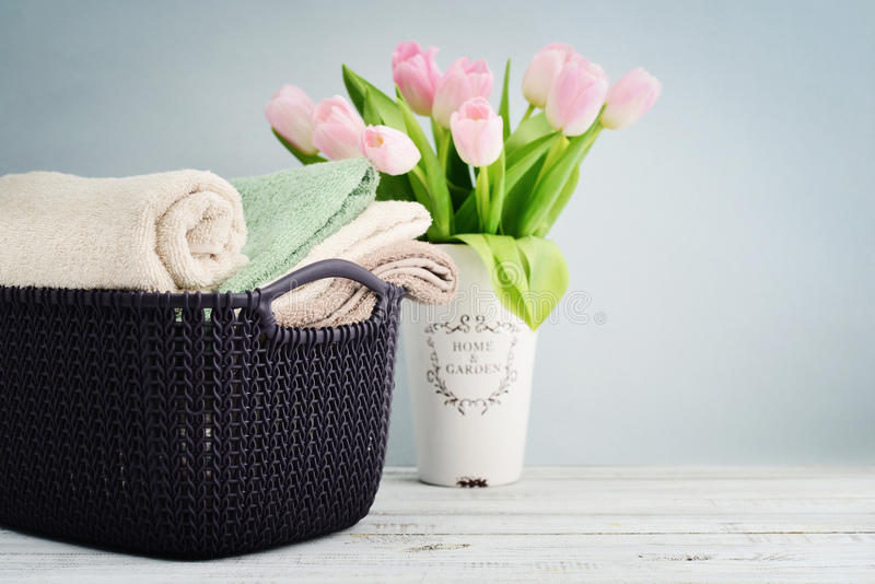 Bath towels of different colors in wicker basket royalty free stock image