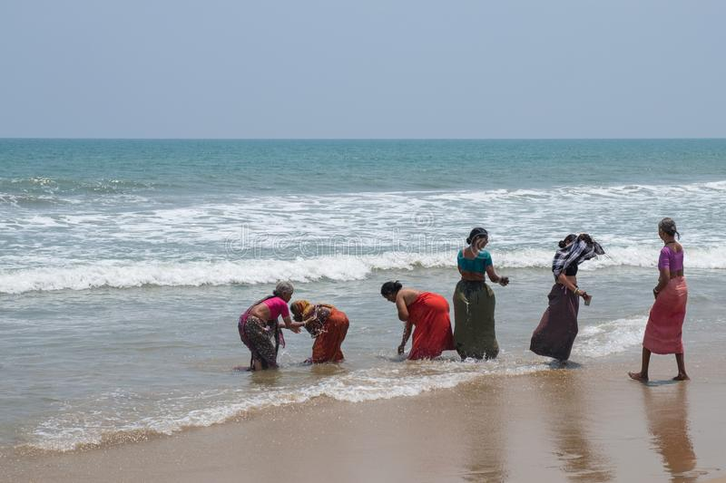 Bathers in the Bay of Bengal. Mahabalipuram, India - March 20, 2018: Women on the beach enjoying the refreshing waters of the Bay of Bengal on the Coromandel royalty free stock photography