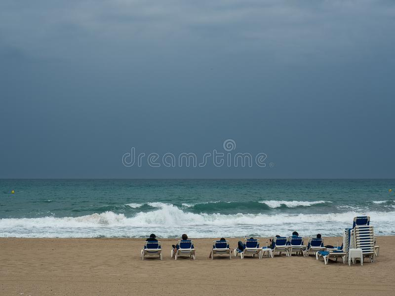 Bathers contemplating the sea sitting in Loungers. Of blue color royalty free stock photography