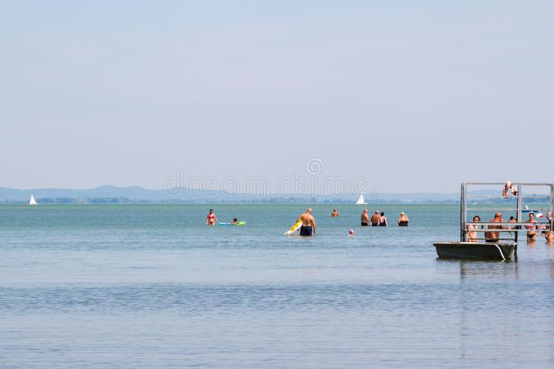 Bathers standing in shallow water of lake. Balaton, Hungary royalty free stock image