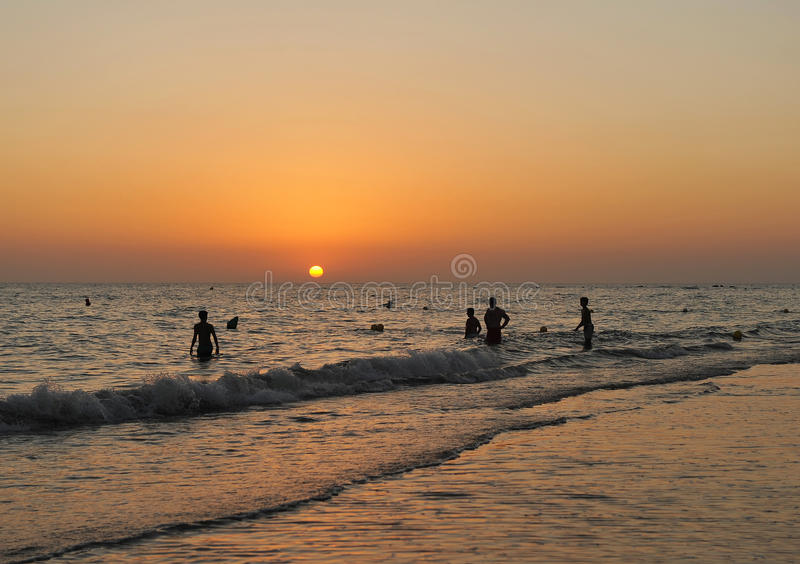 Bathers in the sunset, Cádiz coast, Andalusia, Spain royalty free stock image