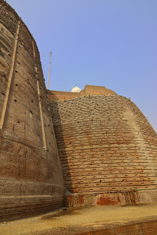 Bathinda fort walls. Entrance to bathinda fort in punjab with rounded walls and a gurdwara at the top under a clear blue sky stock images
