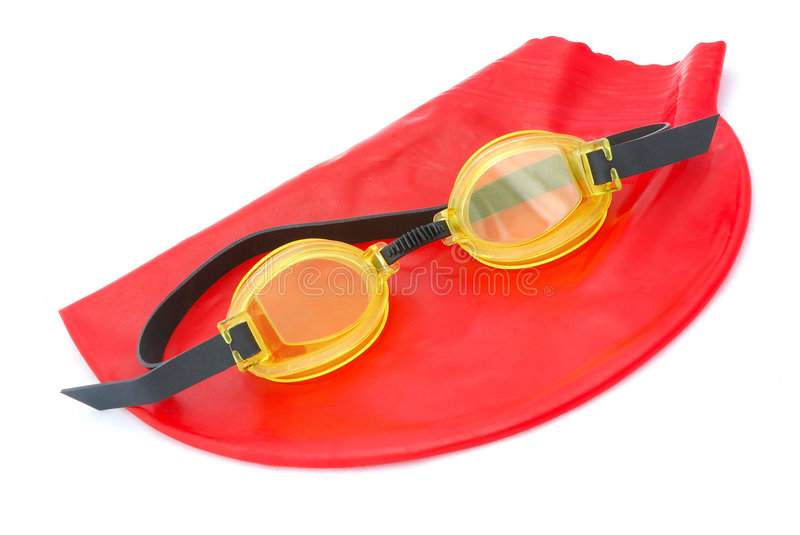 Bathing cap with goggles. A red rubber swimming cap and yellow goggles. Image isolated on white studio background stock image