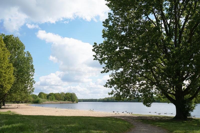 Bathing lake with empty beach in spring. Local recreation area Altwarmbuchener See near Hannover in Germany royalty free stock photos