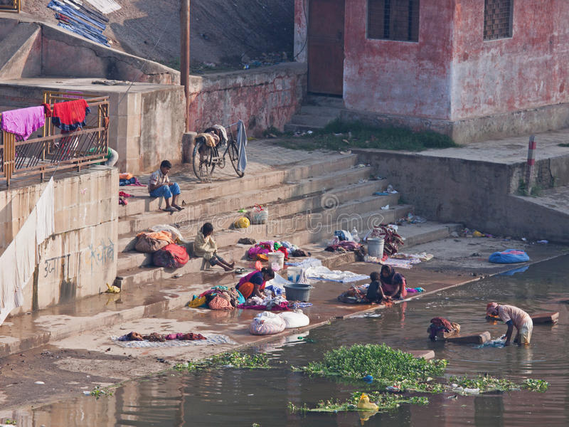 Bathing and washing at the local ghat at Khajuraho, India. VARANASI, INDIA - MARCH 4, 2015: Local people, many of whom do not have access to a domestic water stock photography