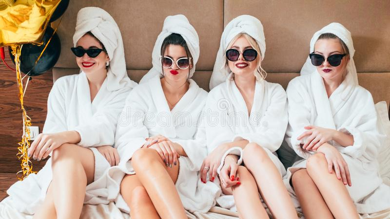 Bathrobe girls bed watching expressions emotions. Movie time. Bathrobe girls sitting in row on bed. Watching. Facial expressions and emotions. Sunglasses and royalty free stock photo
