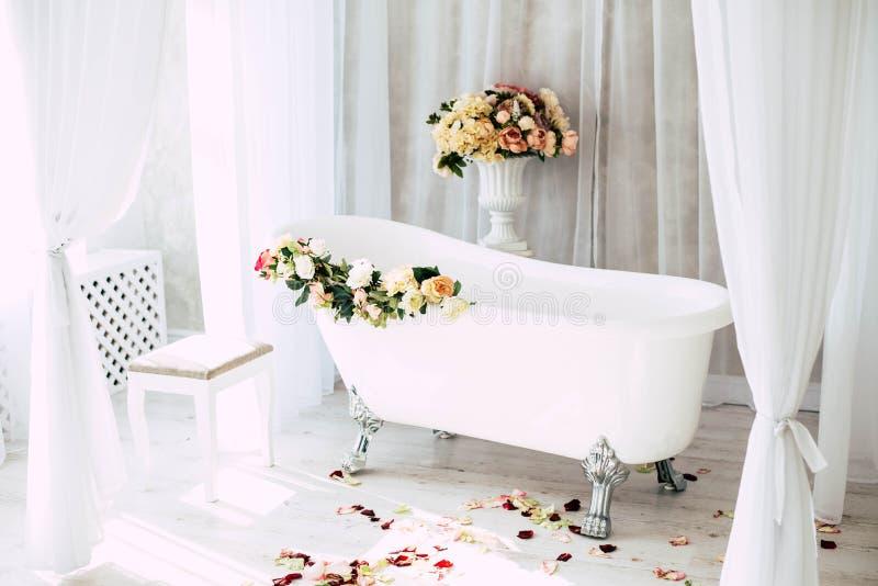 Bathroom в светлой комнате украшенной с цветками и лепестками роз стоковое фото
