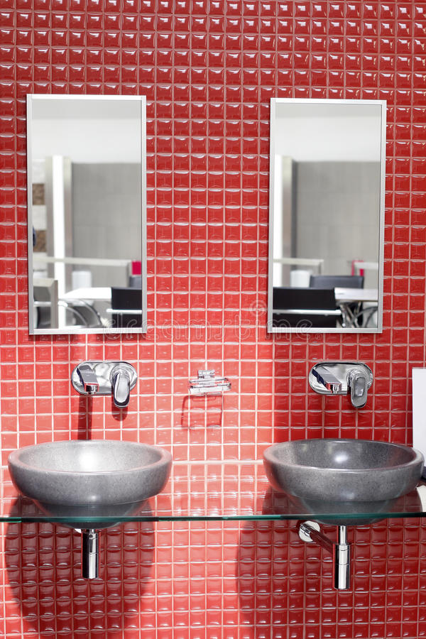Bathroom. Modern bathroom interior with twin washstands, mirrors and tiled walls stock image