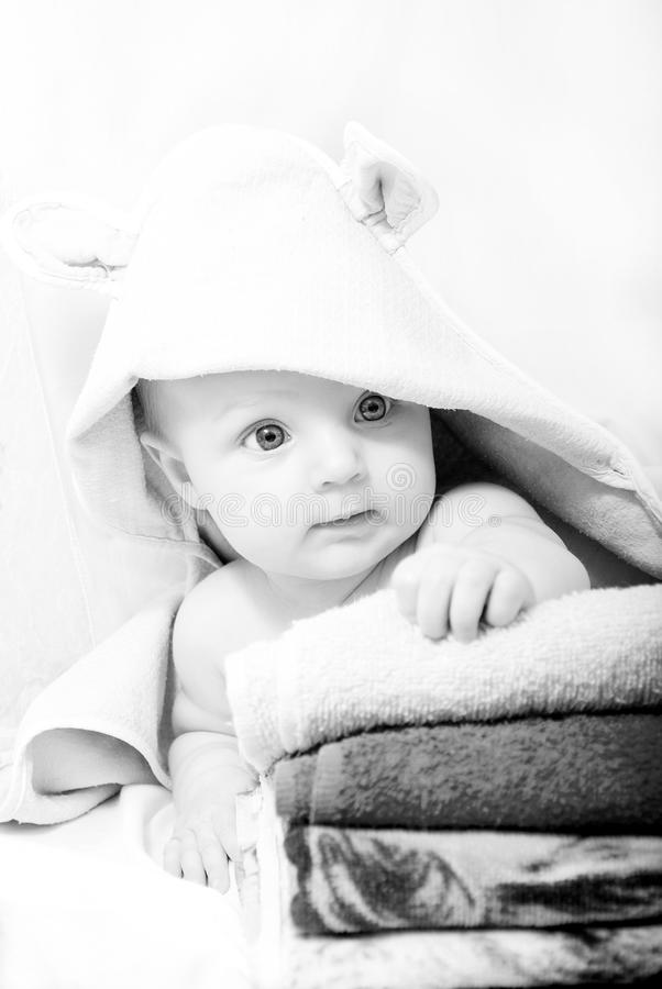 The little girl after bath on the towel in a dressing gown. Black and white photo of a little girl after bath on the towel in a dressing gown on a white stock photos