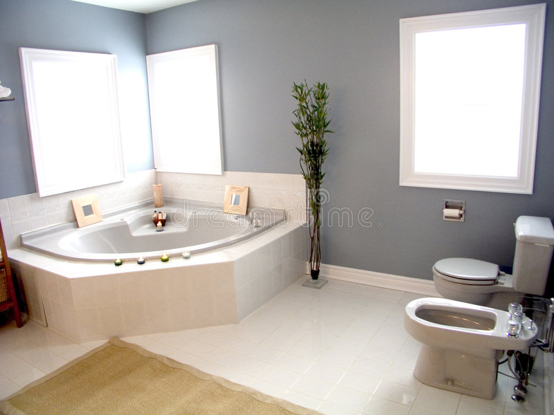 Bathroom 41. Bathroom with windows, white porcelain fixtures, plant, pastel walls and whirlpool bathtub with candles
