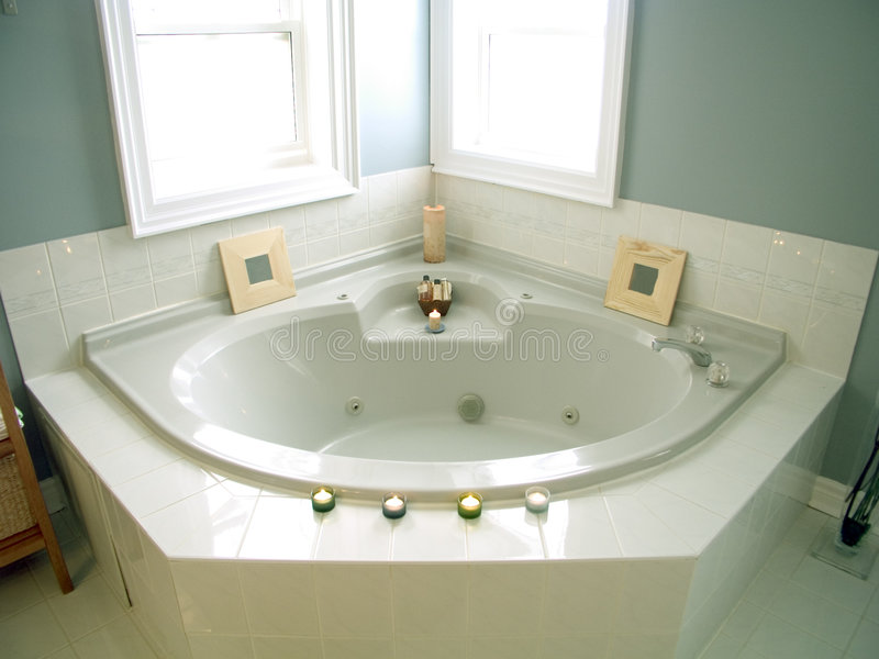 Bathroom 44. Bathroom with windows, white porcelain fixtures, plant, pastel walls and whirlpool bathtub with candles