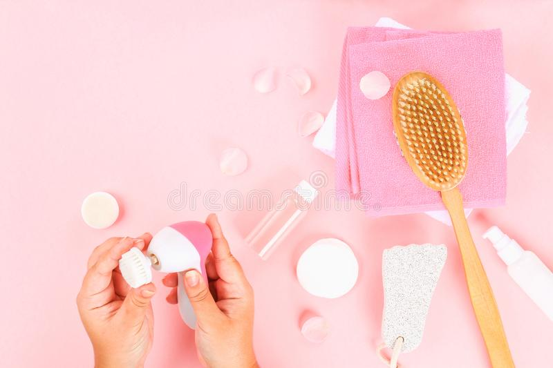 Bathroom accessories on a pastel pink background. Top view, copy space. Brush, loofah, towels, lotion, cream, pence. Face cleansin. G brush in hand stock photo