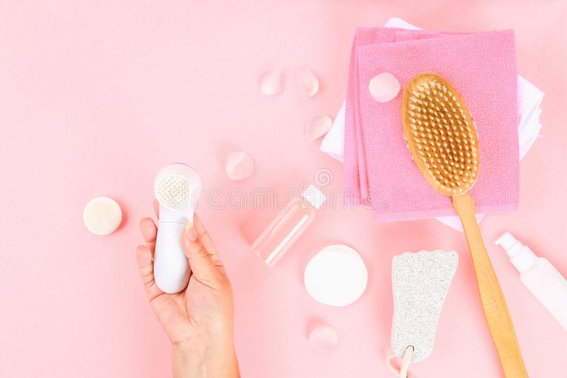Bathroom accessories on a pastel pink background. Top view, copy space. Brush, loofah, towels, lotion, cream, pence. Face cleansin. G brush in hand stock photography