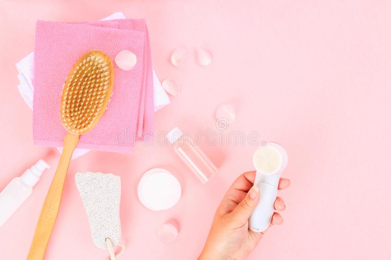 Bathroom accessories on a pastel pink background. Top view, copy space. Brush, loofah, towels, lotion, cream, pence. Face cleansin. G brush in hand royalty free stock photography