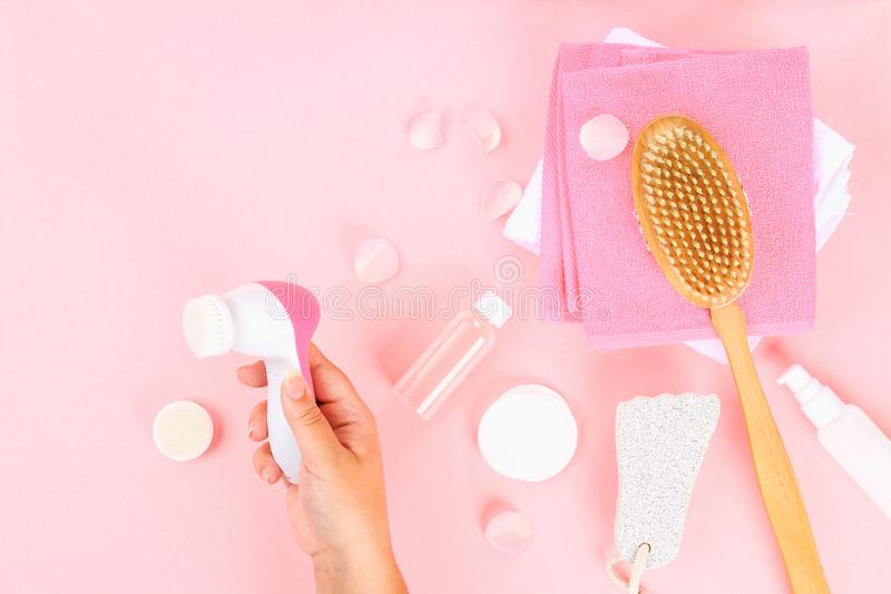 Bathroom accessories on a pastel pink background. Top view, copy space. Brush, loofah, towels, lotion, cream, pence. Face cleansin. G brush in hand royalty free stock photo