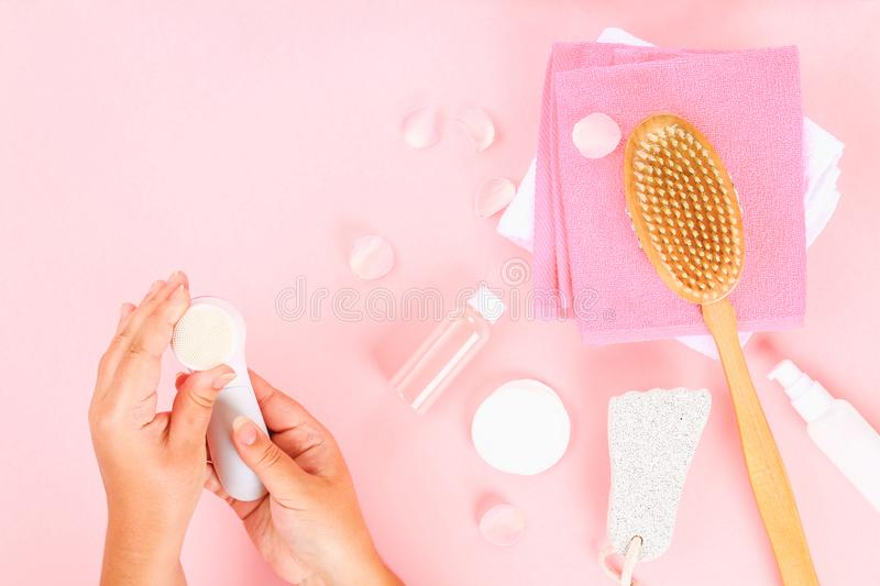 Bathroom accessories on a pastel pink background. Top view, copy space. Brush, loofah, towels, lotion, cream, pence. Face cleansin. G brush in hand royalty free stock photos
