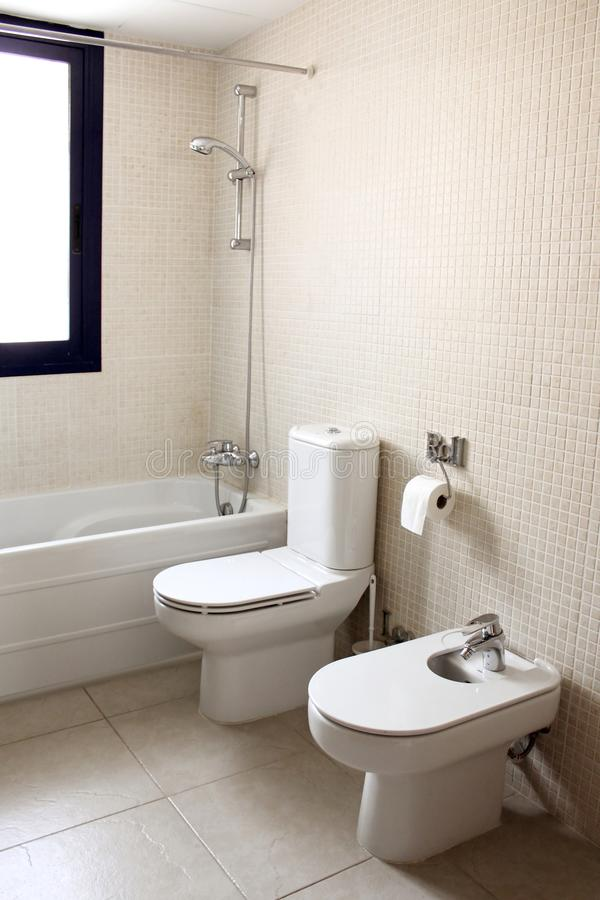 Bathroom with bath toilet and bidet. Window natural light cream color royalty free stock photography