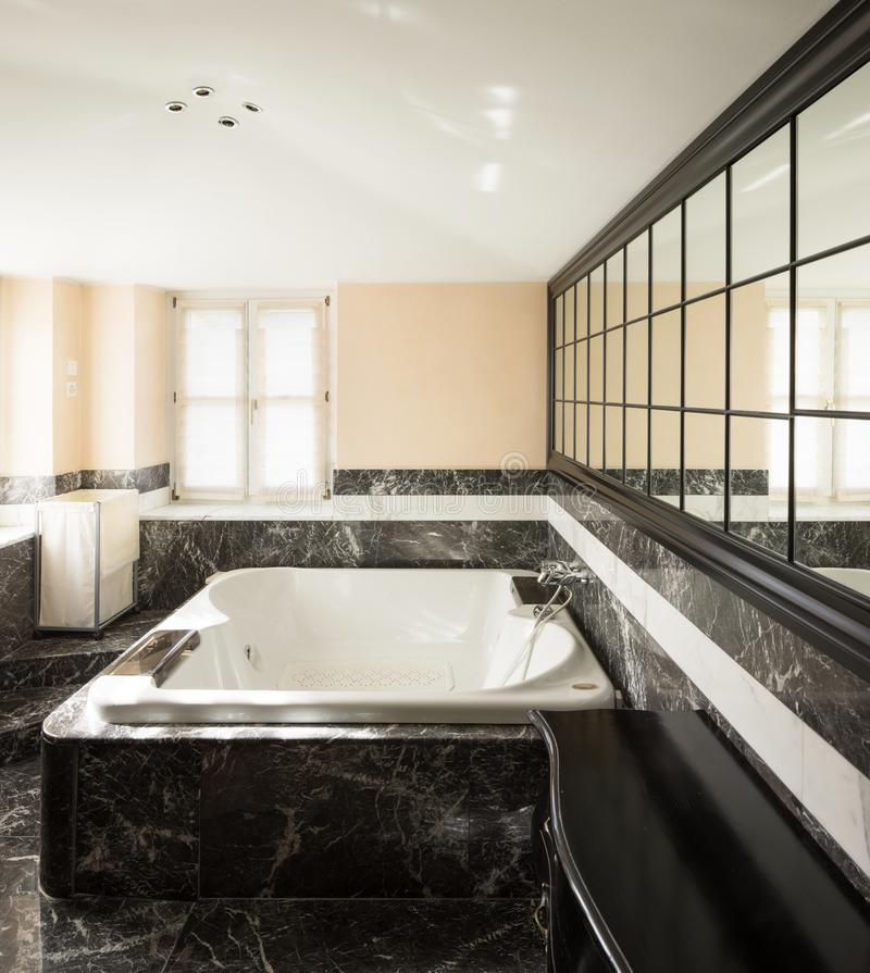 Bathroom with black marble tiles and empty big bathtub stock photography