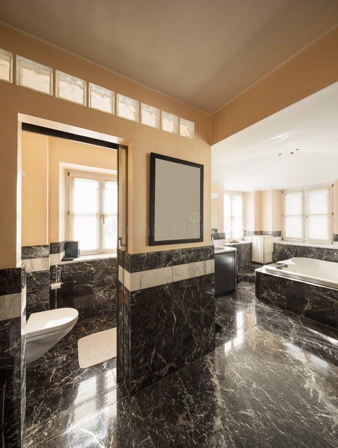 Bathroom with black marble tiles and empty big bathtub stock photo