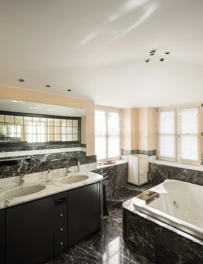 Bathroom with black marble tiles and empty big bathtub royalty free stock images