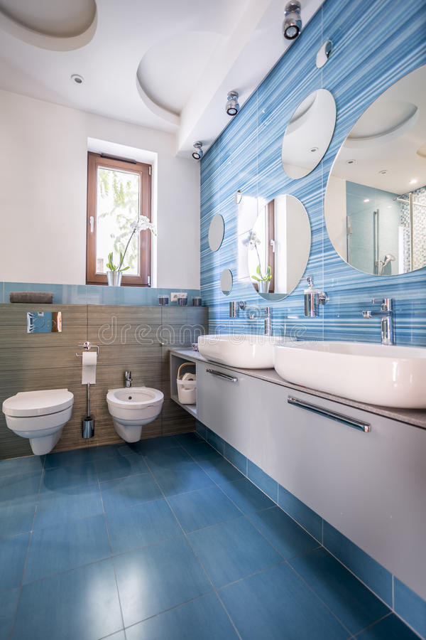 Bathroom with blue tiles and mirrors. Contemporary bathroom with blue decorative tiles and round mirrors royalty free stock photos