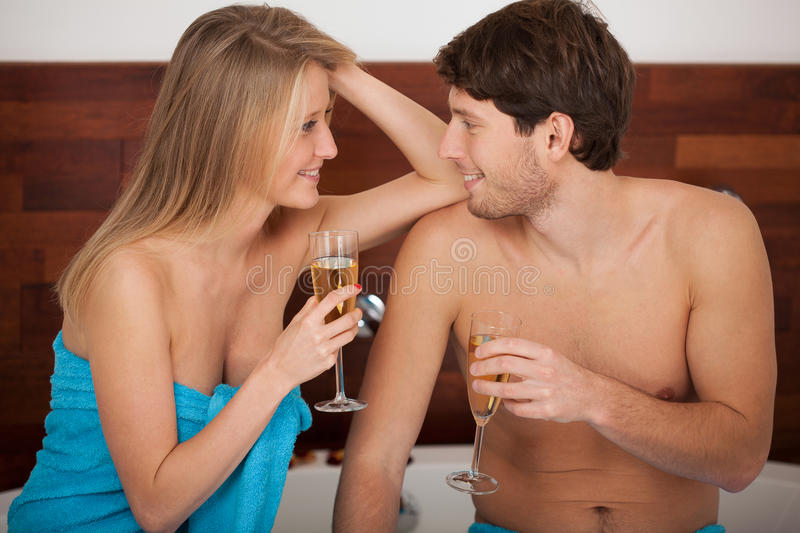 Bathroom champagne toast. A couple proposing a toast with champagne in the bathroom royalty free stock photo