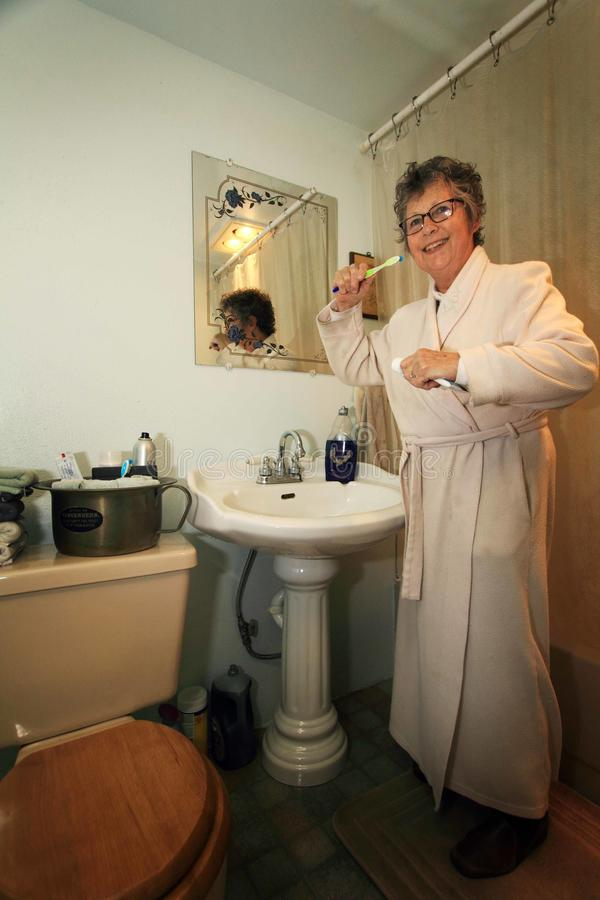 Bathroom chores. An older woman in a long housecoat standing in the bathroom getting ready to brush her teeth stock photo