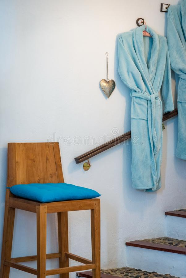 Bathroom detail shot with bath robe bathrobe hanging on the wall and a high decoration chair in front next to stairs royalty free stock photo