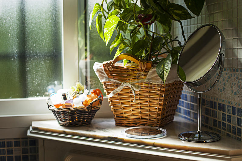Bathroom. With a green plant inside a basket, two mirrors and another basket with soaps. The elements are illuminated by the window stock image