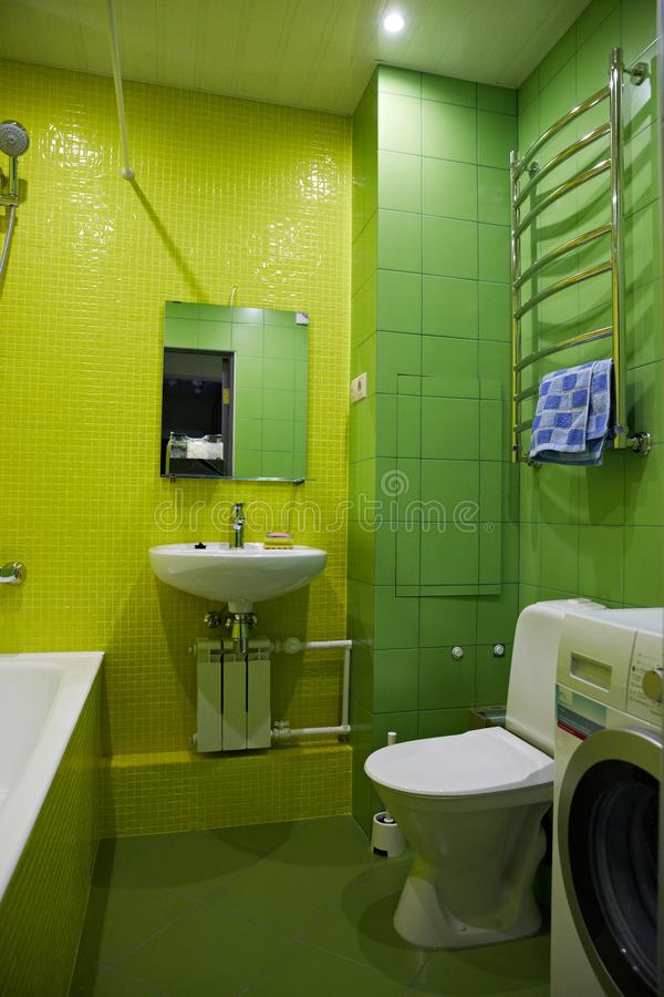 Bathroom in green and yellow. Toilet bowl, sink, washing machine, bathtub.  royalty free stock photography