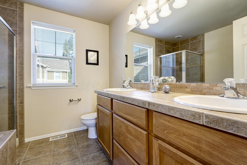 Bathroom interior in beige and brown colors. Wooden double sink vanity cabinet with large mirror, toilet and shower. Northwest, USA stock images