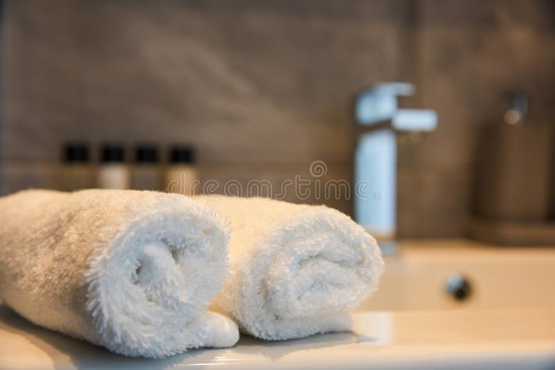 Luxury bathroom sink and white towels. Closeup view with details. Bathroom interior. Blur sink and white roll ups of hand towels. Closeup view with details royalty free stock photo