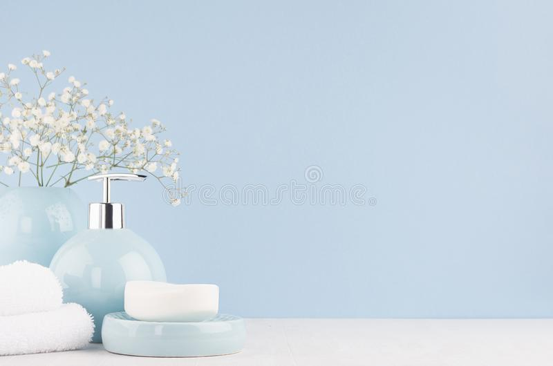 Bathroom interior - ceramic accessories - light blue circle vase with white flowers, soap dispenser , fluffy towels on white wood. Bathroom interior - ceramic royalty free stock photos