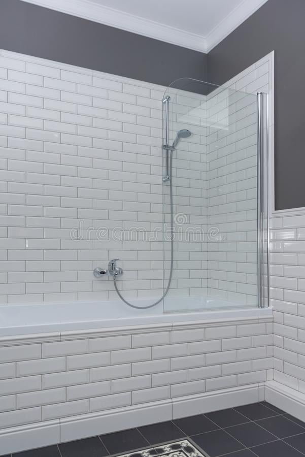 Bathroom interior close-up. The walls are painted gray, covered with decorative ceramic tiles with white glossy bricks. royalty free stock photos