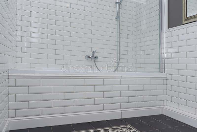 Bathroom interior close-up. The walls are painted gray, covered with decorative ceramic tiles with white glossy bricks. royalty free stock image