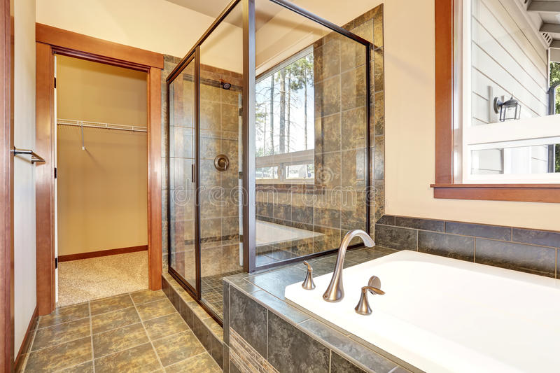 Bathroom interior with marble tile trim. View of glass shower cabin. And white bath tub. Northwest, USA royalty free stock photo