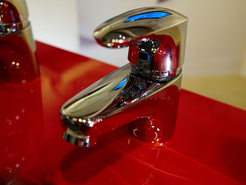 Bathroom interior with modern red sink and silver faucet stock photos