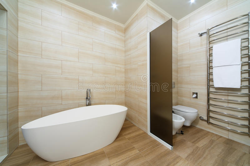 Bathroom interior rooms of the hotel, with a bath, toilet and a. Large heated towel rail stock photo