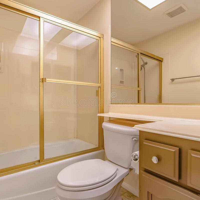 Bathroom interior with sink cabinet and toilet below the large mirror. Square Bathroom interior with sink cabinet and toilet below the large mirror. The bathtub stock photos