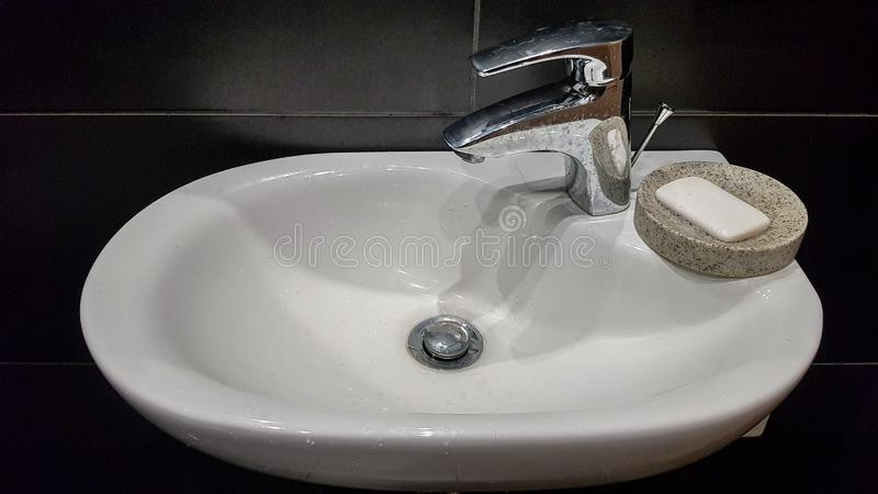 Bathroom interior with sink and faucet. Modern apartment in the attic of the house. White ceramic washbasin with chrome tap on a royalty free stock images