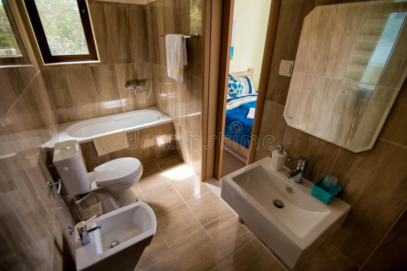Bathroom interior - washbasin, bidet, toilet, large mirror. The walls are light brown in color. Bathroom interior - washbasin, bidet, toilet large mirror stock images